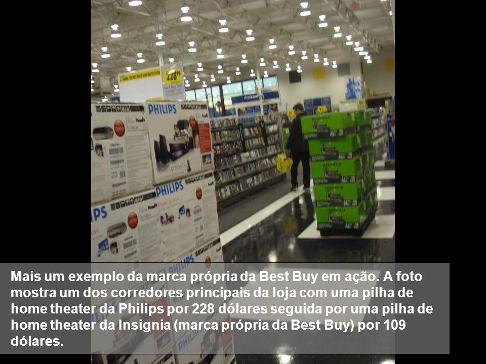 Mais um exemplo da marca própria da Best Buy em ação. A foto mostra um dos corredores principais da loja com uma pilha de home theater da Philips por