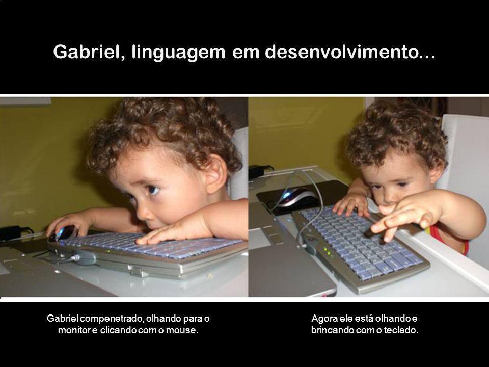 Gabriel, linguagem em desenvolvimento... Gabriel compenetrado, olhando para o monitor e clicando com o mouse. Agora ele está olhando e brincando com o