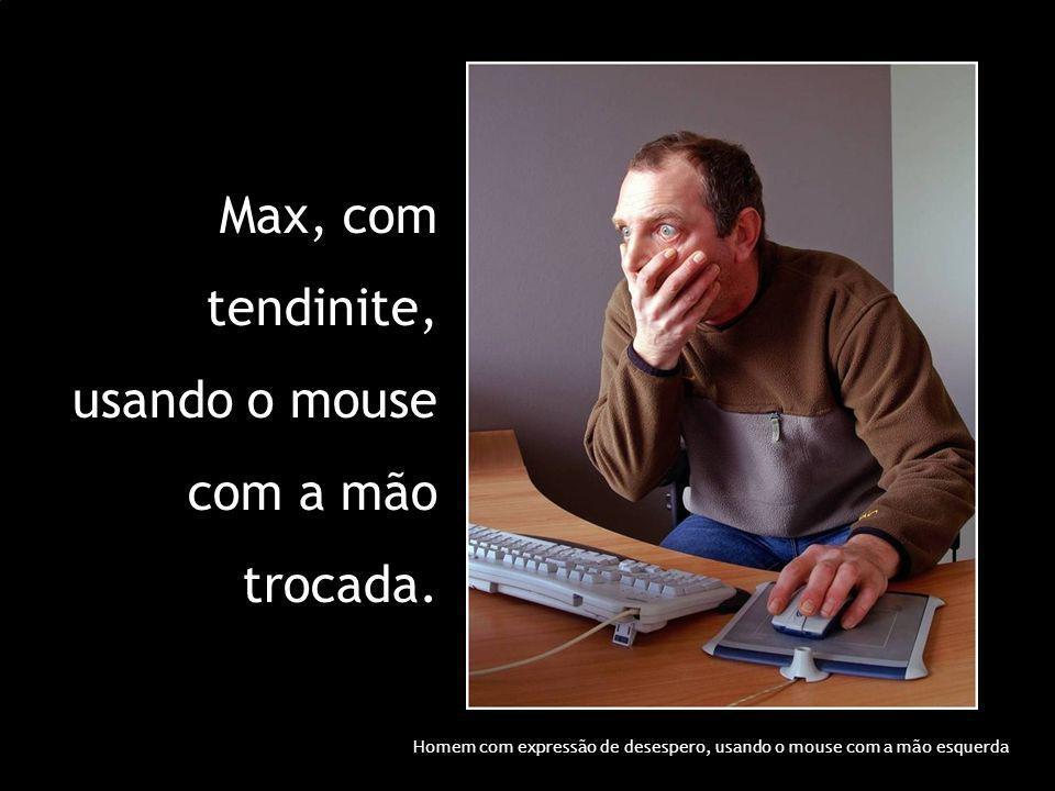 Max, com tendinite, usando o mouse com a mão trocada. Homem com expressão de desespero, usando o mouse com a mão esquerda