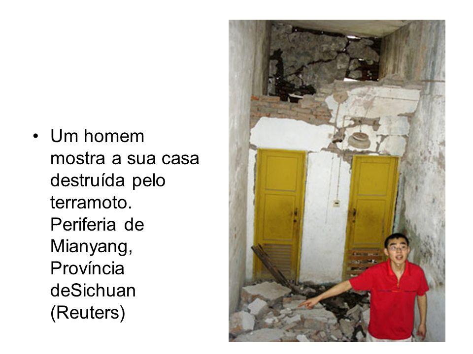 Um homem mostra a sua casa destruída pelo terramoto.