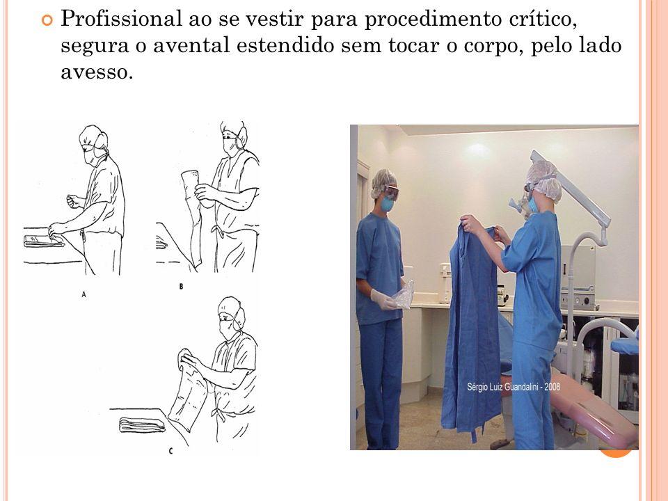 Profissional ao se vestir para procedimento crítico, segura o avental estendido sem tocar o corpo, pelo lado avesso.
