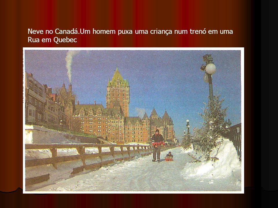 Neve no Canadá.Um homem puxa uma criança num trenó em uma Rua em Quebec