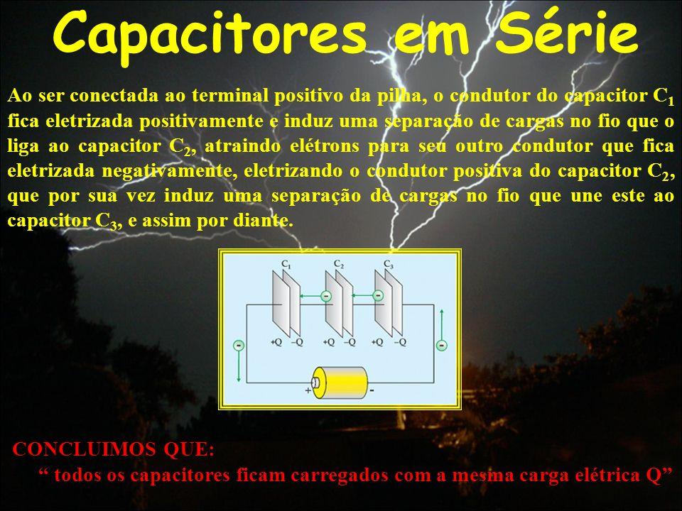 Capacitores em Série Ao ser conectada ao terminal positivo da pilha, o condutor do capacitor C 1 fica eletrizada positivamente e induz uma separação d