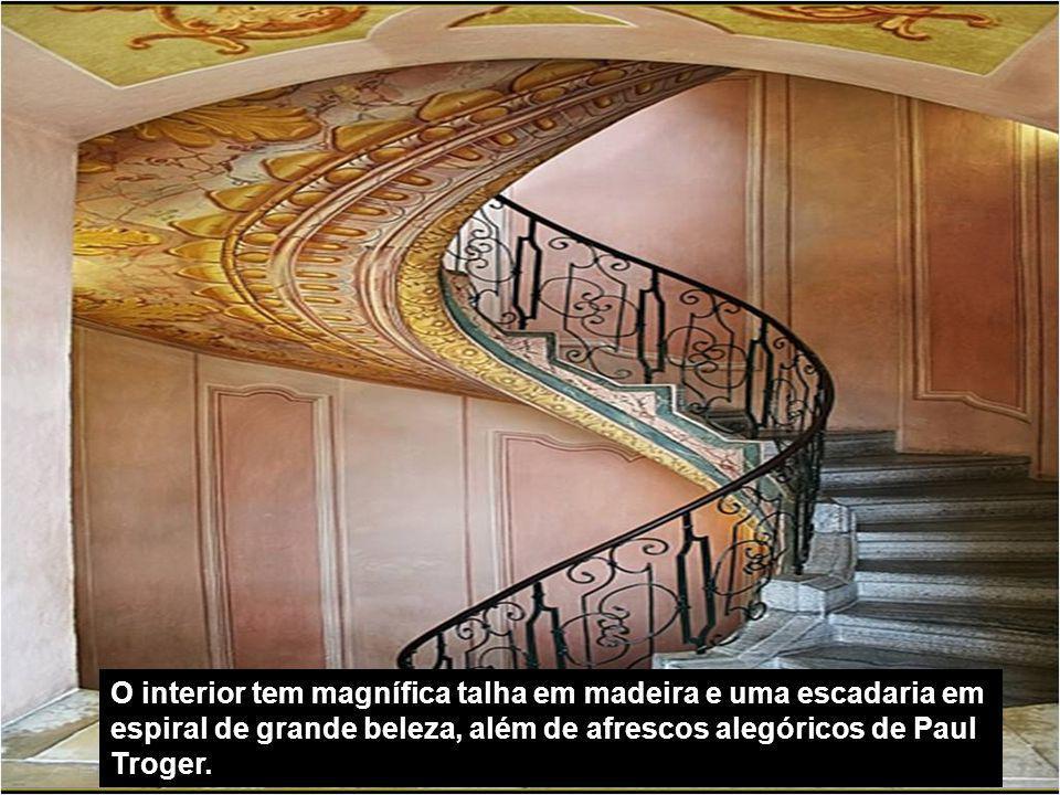 O interior tem magnífica talha em madeira e uma escadaria em espiral de grande beleza, além de afrescos alegóricos de Paul Troger.