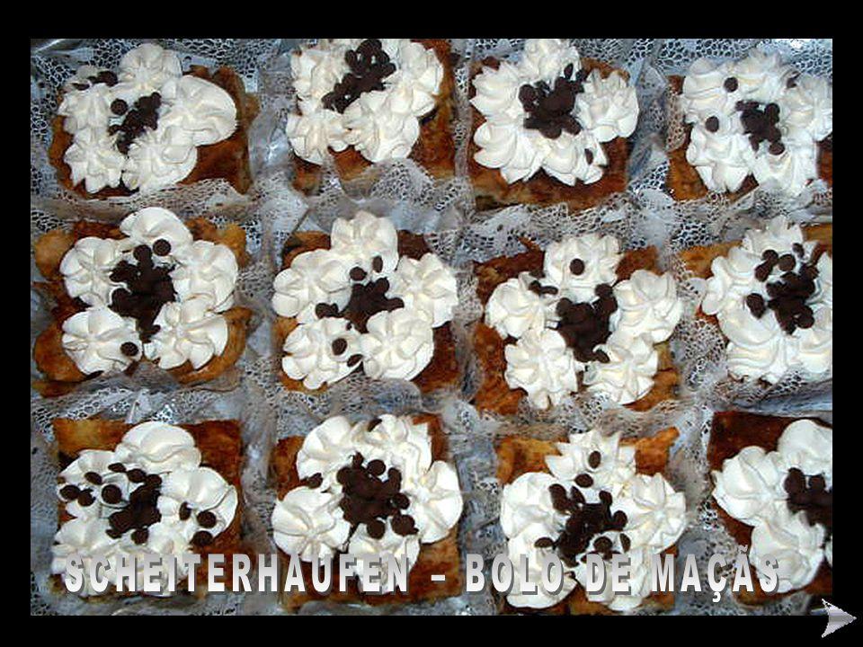 SCHEITERHAUFEN – BOLO ALEMÃO DE MAÇÃS – PASSO A PASSO Ingredientes: 12 pãezinhos cortados em rodelas finas (franceses ou de água – amanhecidos) 10 maçãs gigantes ou 14 médias e ácidas raladas grossas com as cascas 1 xícara (chá) de nozes picadinhas 2 a 3 xícaras (chá) de passas pretas sem sementes 3 xícaras (chá) de açúcar suco de 2 a 3 limões grandes casca ralada de 2 limões 1 litro de leite 4 ovos gigantes 1 colher (chá – rasa) de sal 1 colher (sopa) de açúcar de baunilha pedacinhos de manteiga espalhados por cima (60g).
