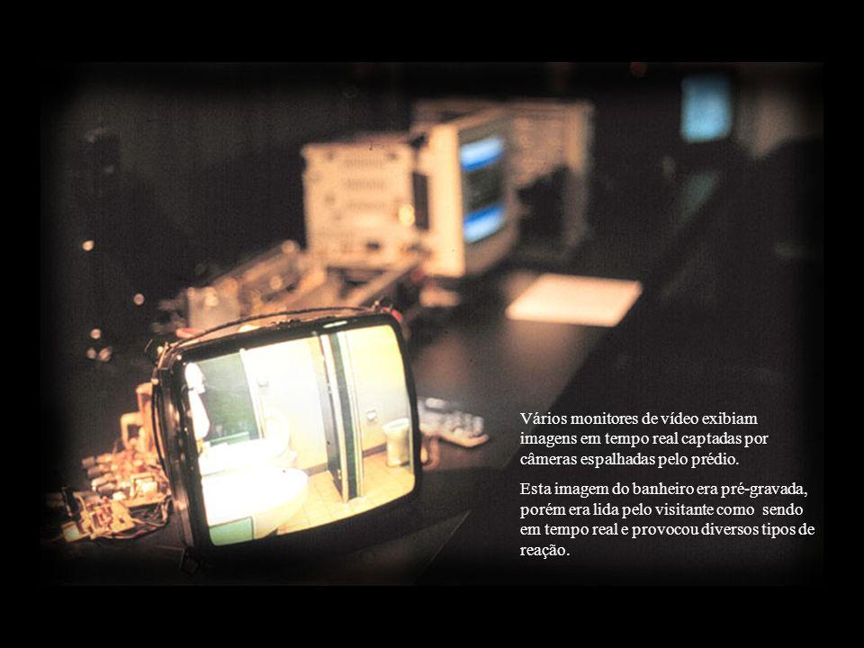 Sala escura com projeção de imagem de vídeo captada por micro-câmera no espaço reservado para os visitantes surfarem nas ondas da Internet.