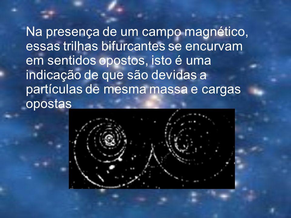 Na presença de um campo magnético, essas trilhas bifurcantes se encurvam em sentidos opostos, isto é uma indicação de que são devidas a partículas de