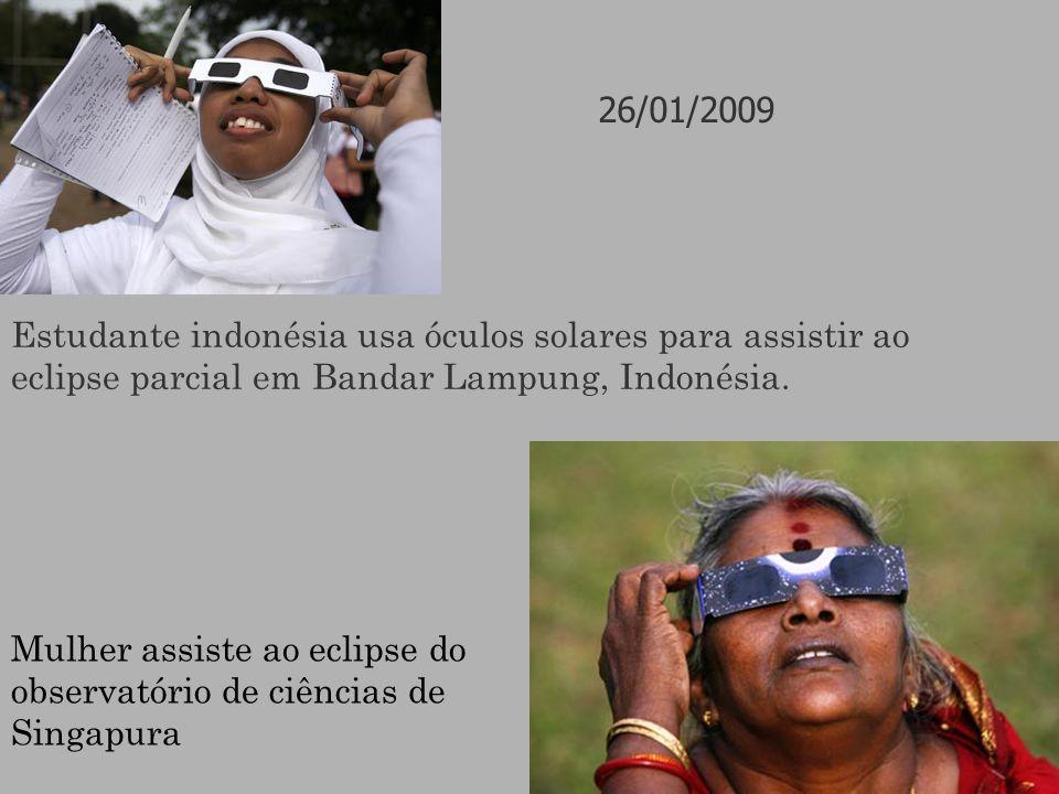 Estudante indonésia usa óculos solares para assistir ao eclipse parcial em Bandar Lampung, Indonésia. Mulher assiste ao eclipse do observatório de ciê
