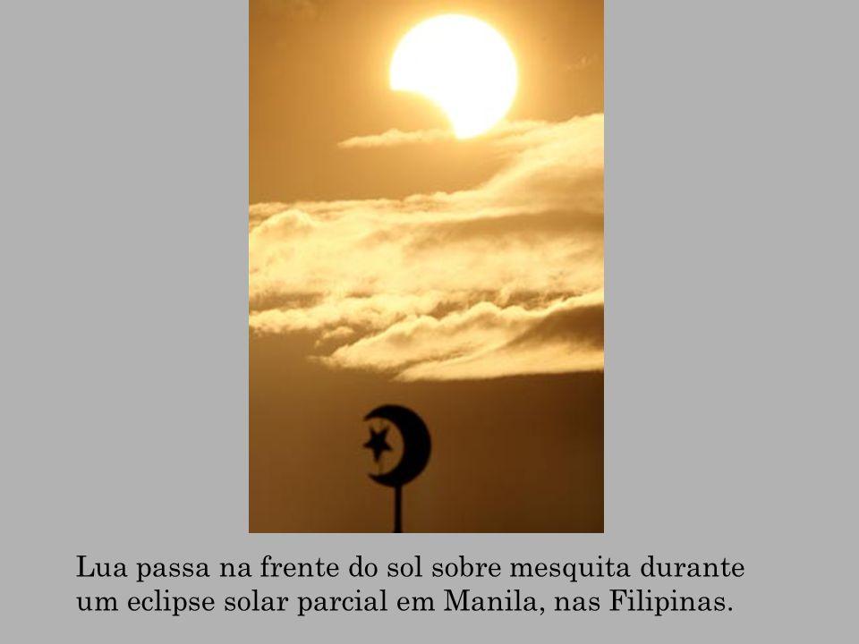 Lua passa na frente do sol sobre mesquita durante um eclipse solar parcial em Manila, nas Filipinas.