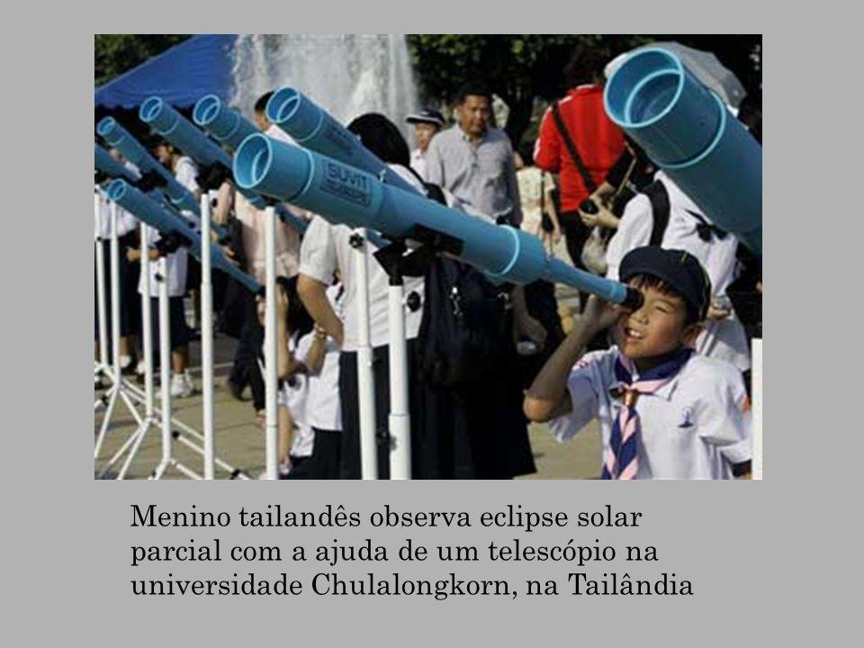 Menino tailandês observa eclipse solar parcial com a ajuda de um telescópio na universidade Chulalongkorn, na Tailândia