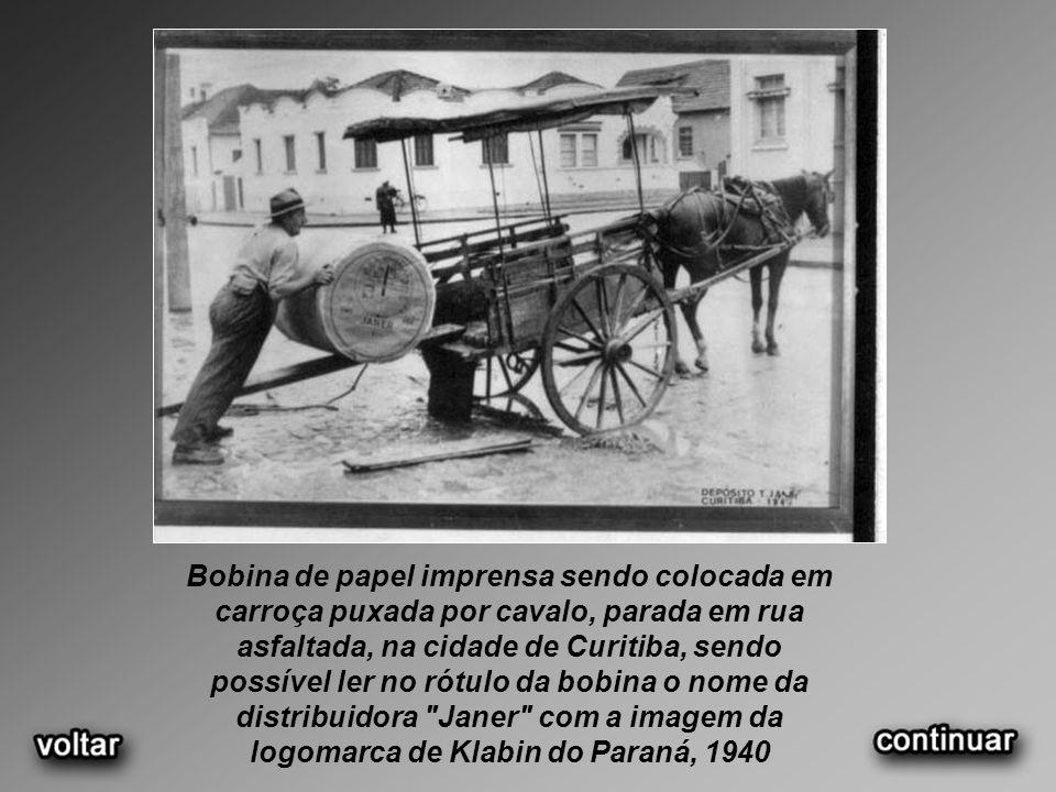 Bobina de papel imprensa sendo colocada em carroça puxada por cavalo, parada em rua asfaltada, na cidade de Curitiba, sendo possível ler no rótulo da