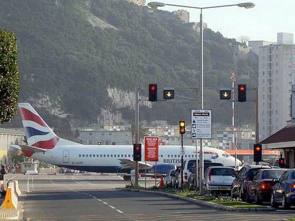 Uma cena pitoresca: carros à direita, aguardando a passagem de um avião no cruzamento.
