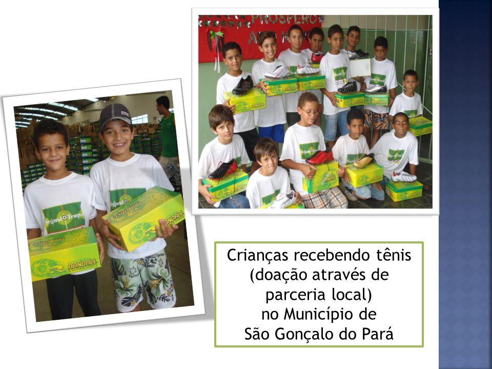 Crianças recebendo tênis (doação através de parceria local) no Município de São Gonçalo do Pará