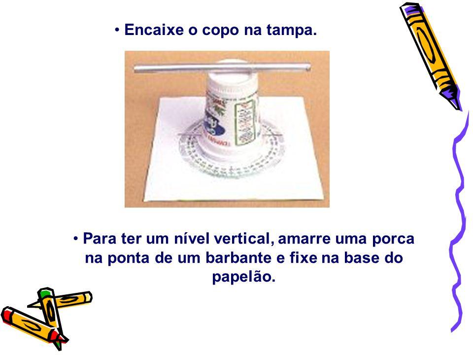 Encaixe o copo na tampa. Para ter um nível vertical, amarre uma porca na ponta de um barbante e fixe na base do papelão.