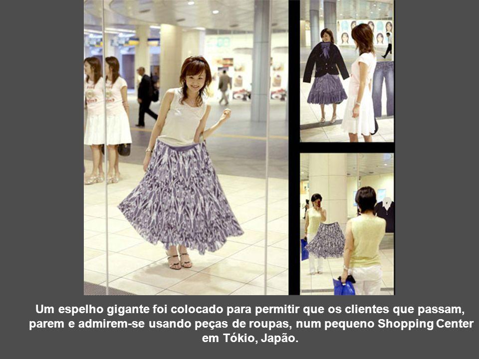 Um espelho gigante foi colocado para permitir que os clientes que passam, parem e admirem-se usando peças de roupas, num pequeno Shopping Center em Tó