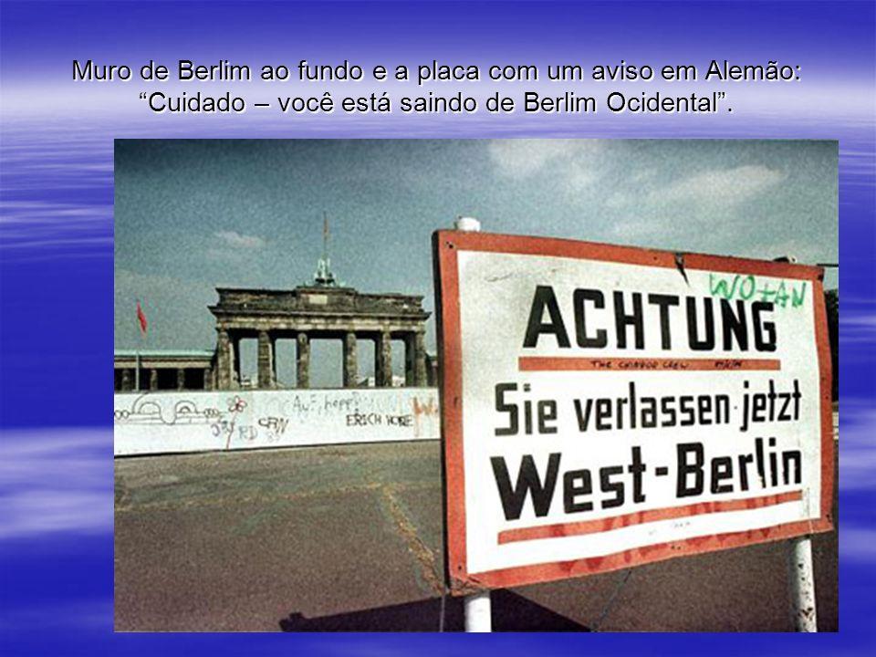 Muro de Berlim ao fundo e a placa com um aviso em Alemão: Cuidado – você está saindo de Berlim Ocidental.