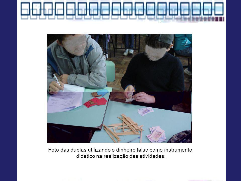 Foto das duplas utilizando o dinheiro falso como instrumento didático na realização das atividades.