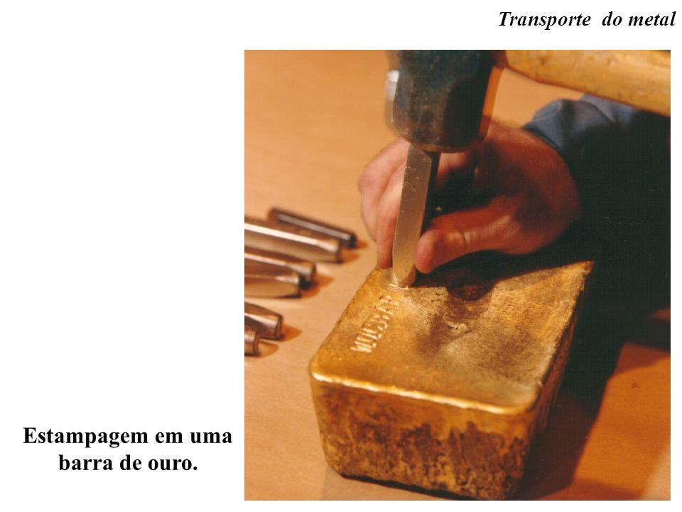 Estampagem em uma barra de ouro. Transporte do metal