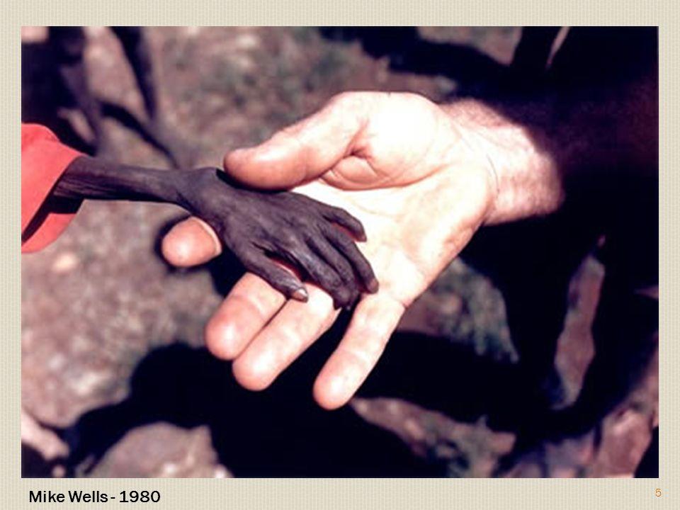 Bastante triste e chocante esta fotografia de uma criança em Uganda provavelmente perto de morrer à fome e um missionário dando-lhe a mão.