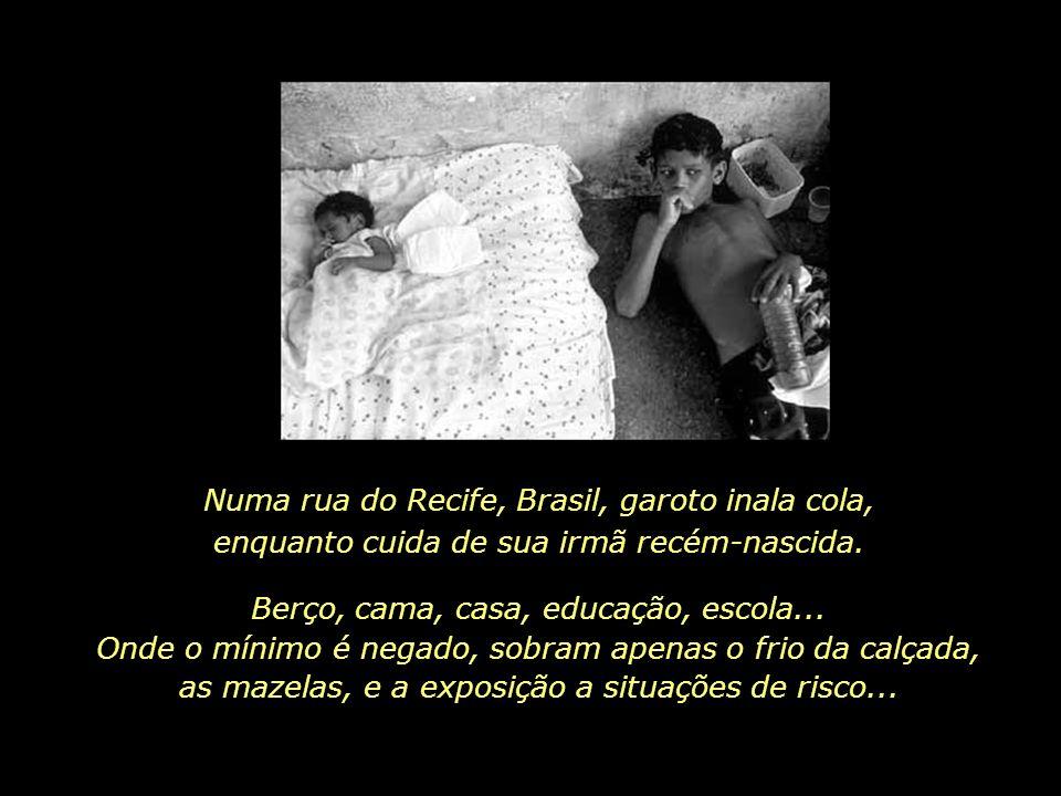 Numa rua do Recife, Brasil, garoto inala cola, enquanto cuida de sua irmã recém-nascida.