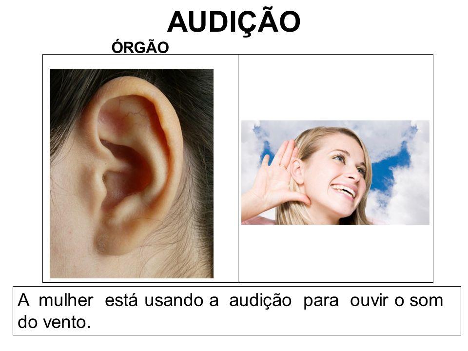 AUDIÇÃO ÓRGÃO A mulher está usando a audição para ouvir o som do vento.