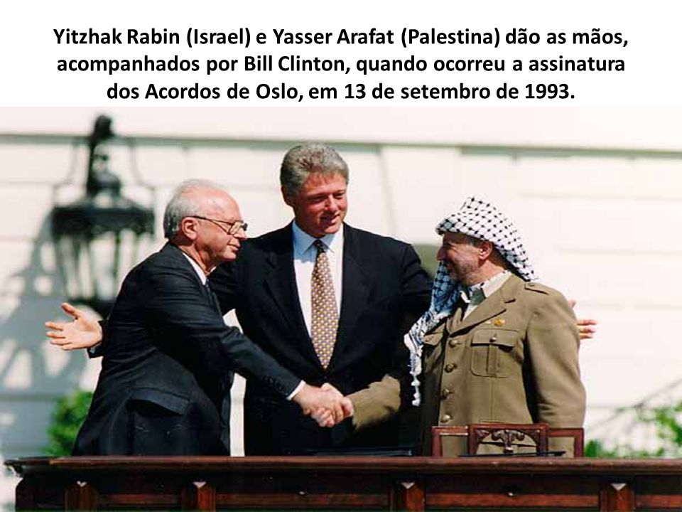 Yitzhak Rabin (Israel) e Yasser Arafat (Palestina) dão as mãos, acompanhados por Bill Clinton, quando ocorreu a assinatura dos Acordos de Oslo, em 13