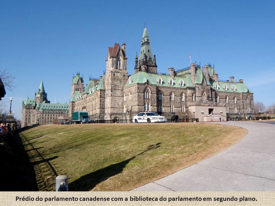 Prédio do parlamento canadense com a biblioteca do parlamento em segundo plano.
