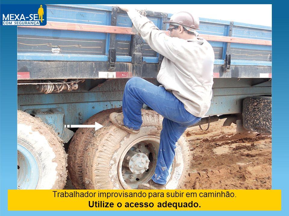 Trabalhador improvisando para subir em caminhão. Utilize o acesso adequado.