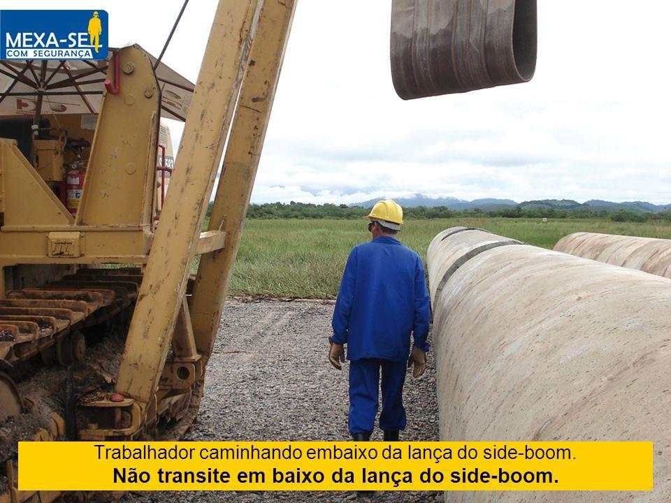 Trabalhador caminhando embaixo da lança do side-boom. Não transite em baixo da lança do side-boom.