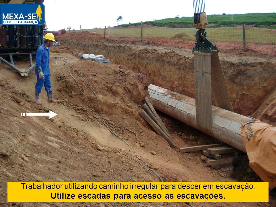Trabalhador utilizando caminho irregular para descer em escavação. Utilize escadas para acesso as escavações.