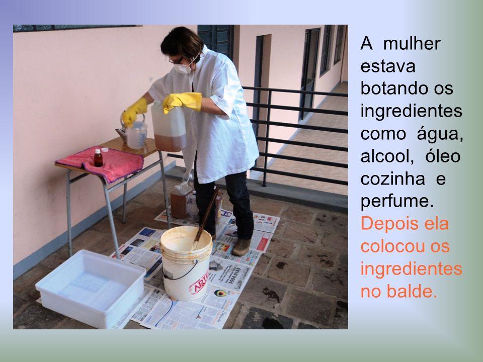 A mulher estava botando os ingredientes como água, alcool, óleo cozinha e perfume. Depois ela colocou os ingredientes no balde.