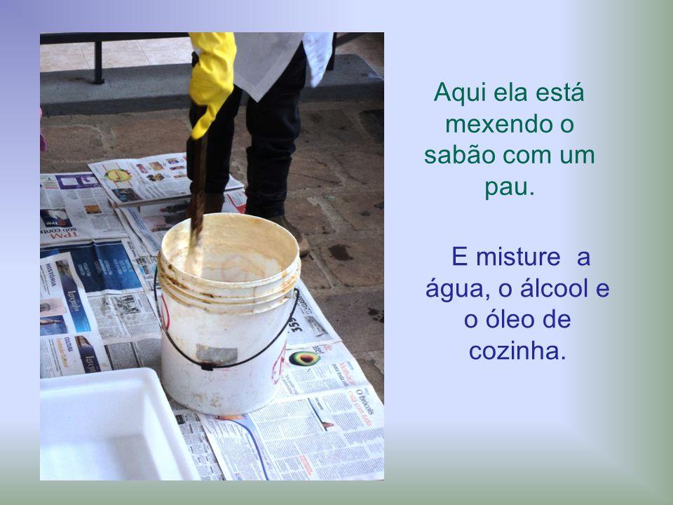 Aqui ela está mexendo o sabão com um pau. E misture a água, o álcool e o óleo de cozinha.