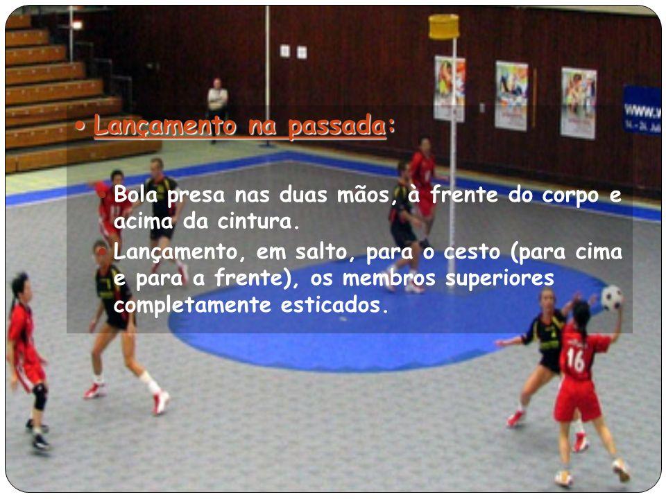 Lançamento na passada: Lançamento na passada: Bola presa nas duas mãos, à frente do corpo e acima da cintura.