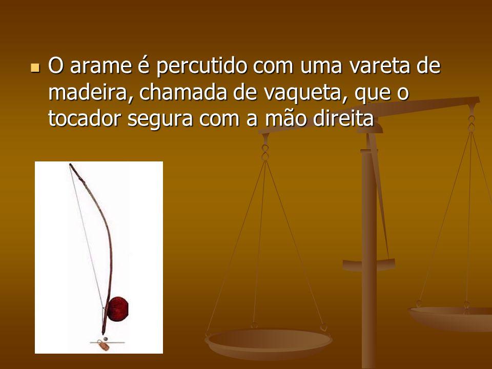 O arame é percutido com uma vareta de madeira, chamada de vaqueta, que o tocador segura com a mão direita O arame é percutido com uma vareta de madeir