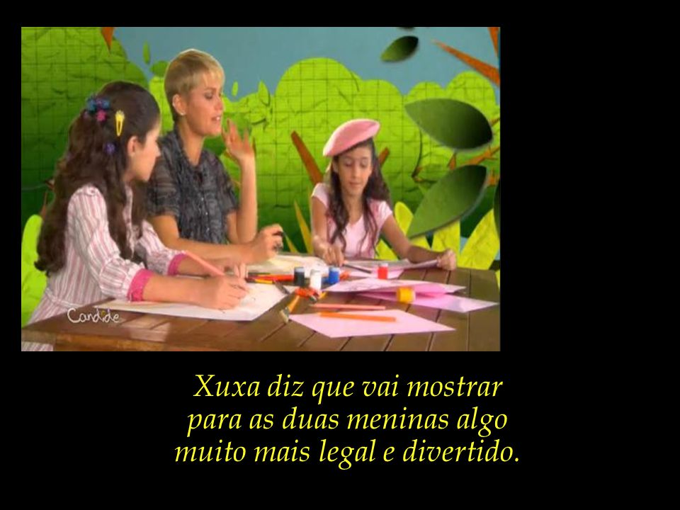 O comercial inicia-se com Xuxa e duas meninas sentadas ao redor de uma mesa com cadernos e lápis de colorir.
