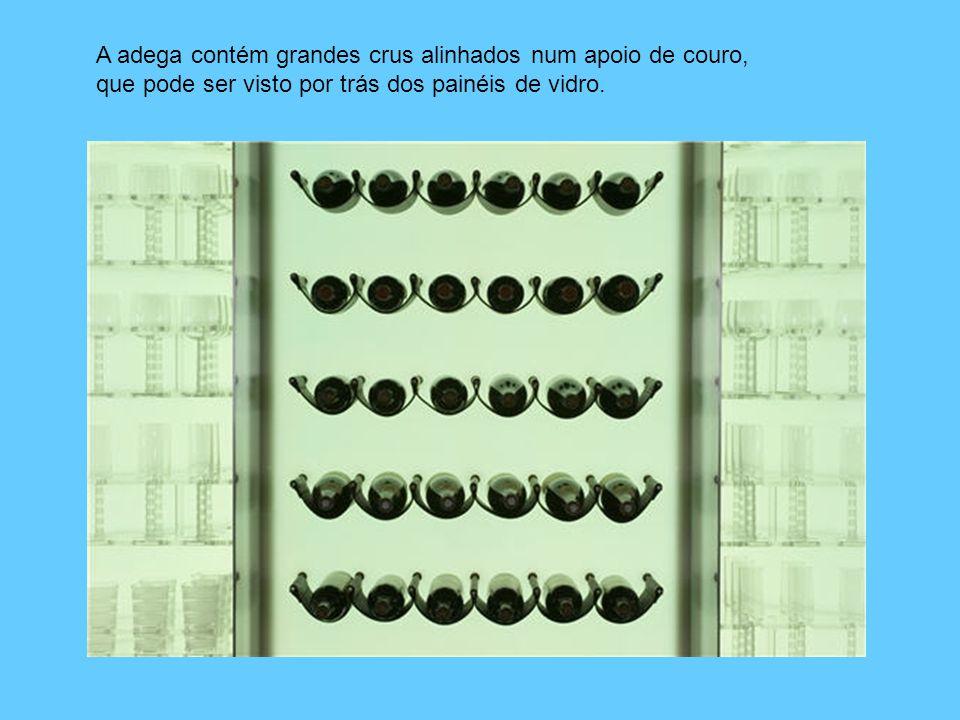 A adega contém grandes crus alinhados num apoio de couro, que pode ser visto por trás dos painéis de vidro.