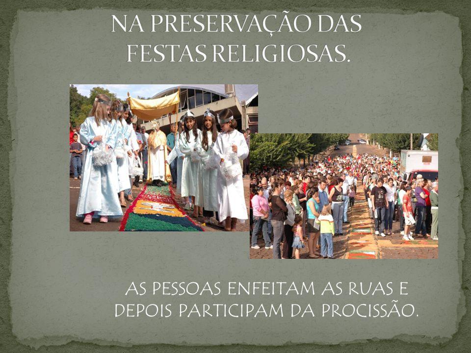 AS PESSOAS ENFEITAM AS RUAS E DEPOIS PARTICIPAM DA PROCISSÃO.