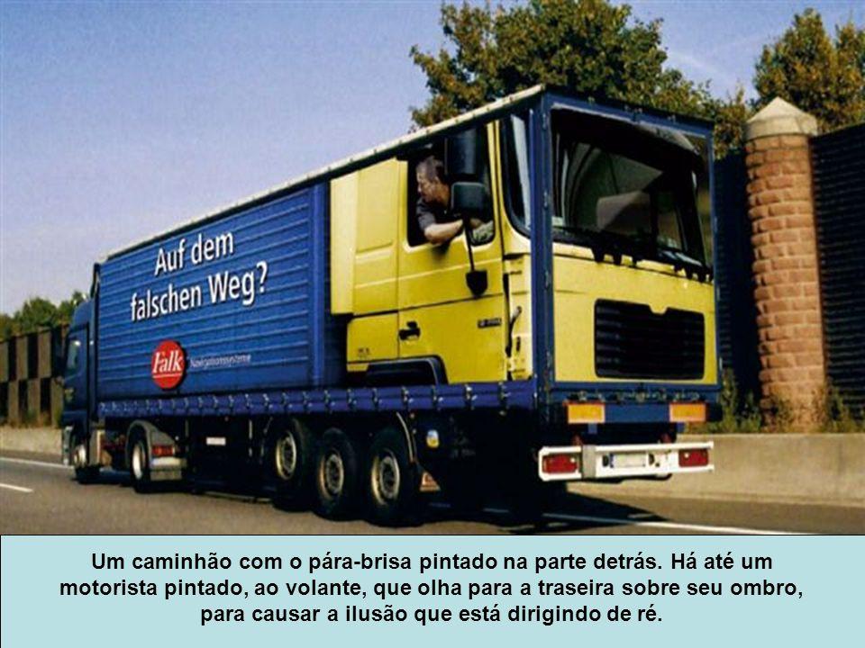 Um caminhão com o pára-brisa pintado na parte detrás. Há até um motorista pintado, ao volante, que olha para a traseira sobre seu ombro, para causar a