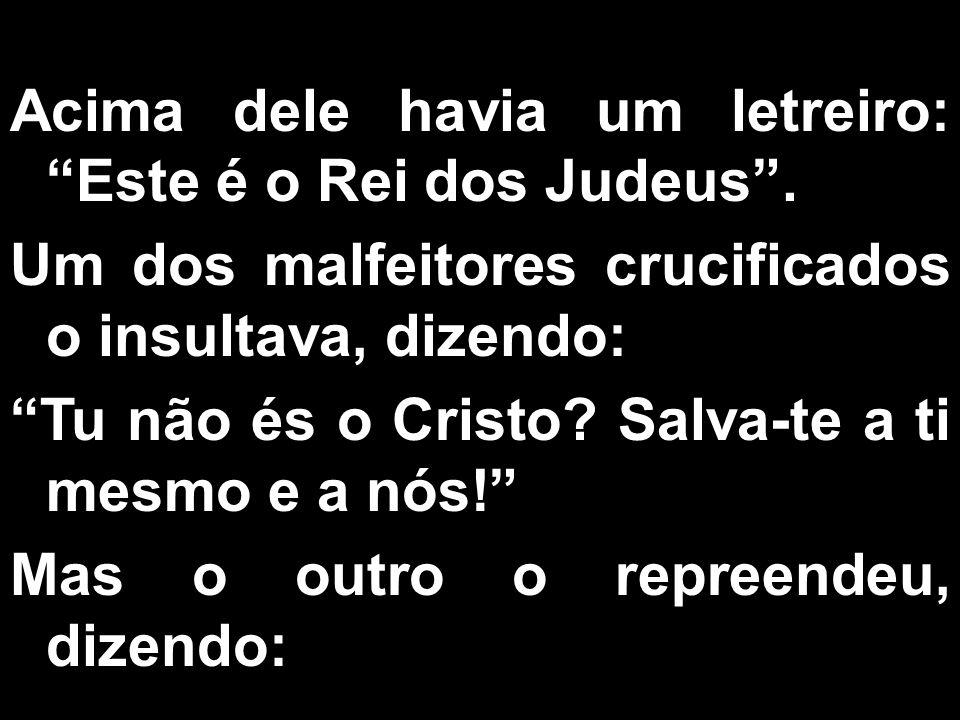 Acima dele havia um letreiro: Este é o Rei dos Judeus. Um dos malfeitores crucificados o insultava, dizendo: Tu não és o Cristo? Salva-te a ti mesmo e