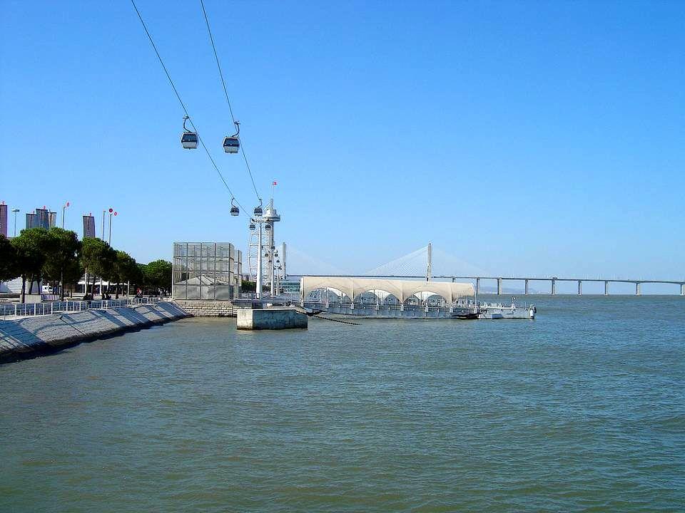 Teleférico que transporta os visitantes de uma ponta à outra na área da antiga exposição. Ao fundo, a Ponte Vasco da Gama.