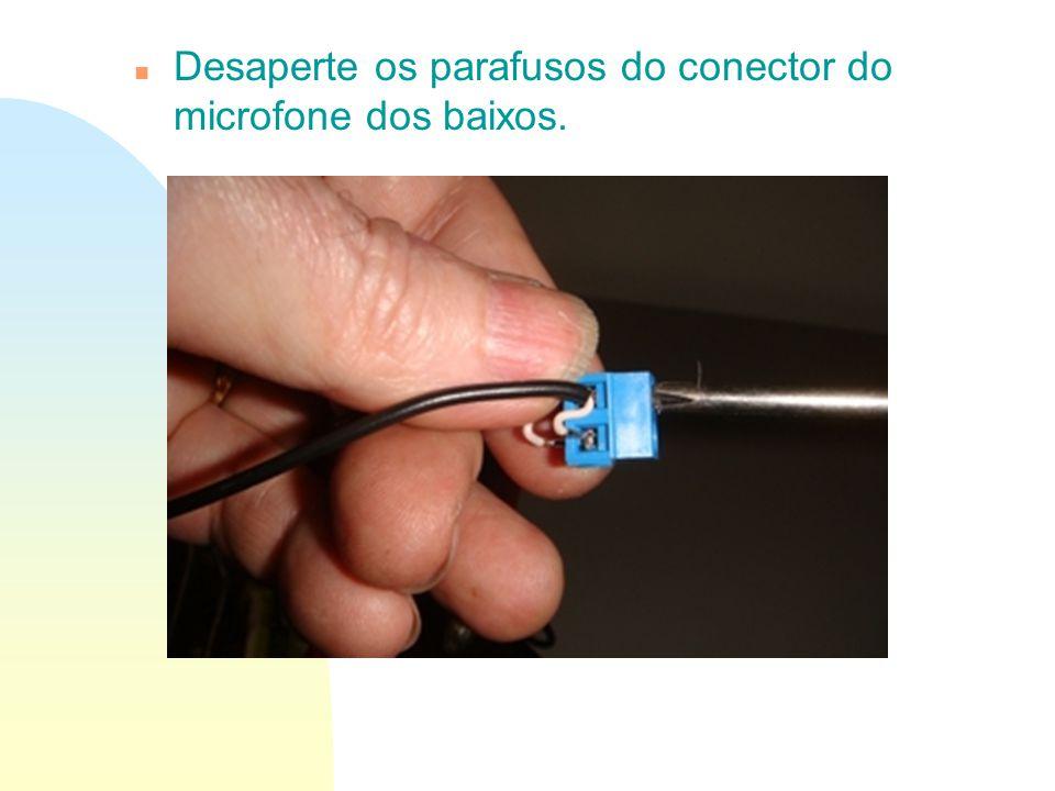 n Desaperte os parafusos do conector do microfone dos baixos.