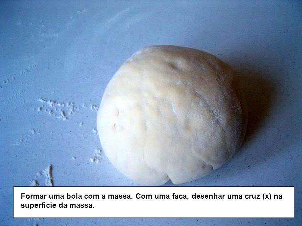 Formar uma bola com a massa. Com uma faca, desenhar uma cruz (x) na superfície da massa.