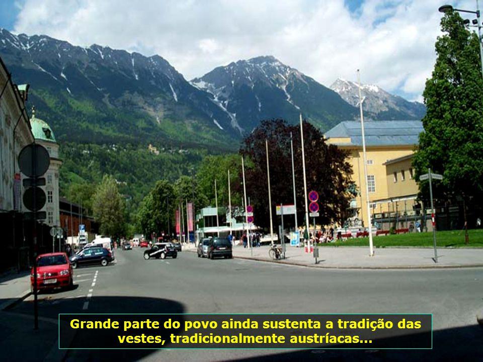Jovens de Innsbruck, curtem o entardecer tranqüilamente na pracinha, tendo ao fundo as montanhas cobertas de neve...