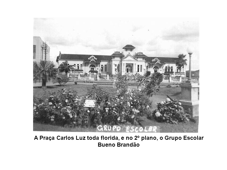 A Praça Carlos Luz toda florida, e no 2º plano, o Grupo Escolar Bueno Brandão