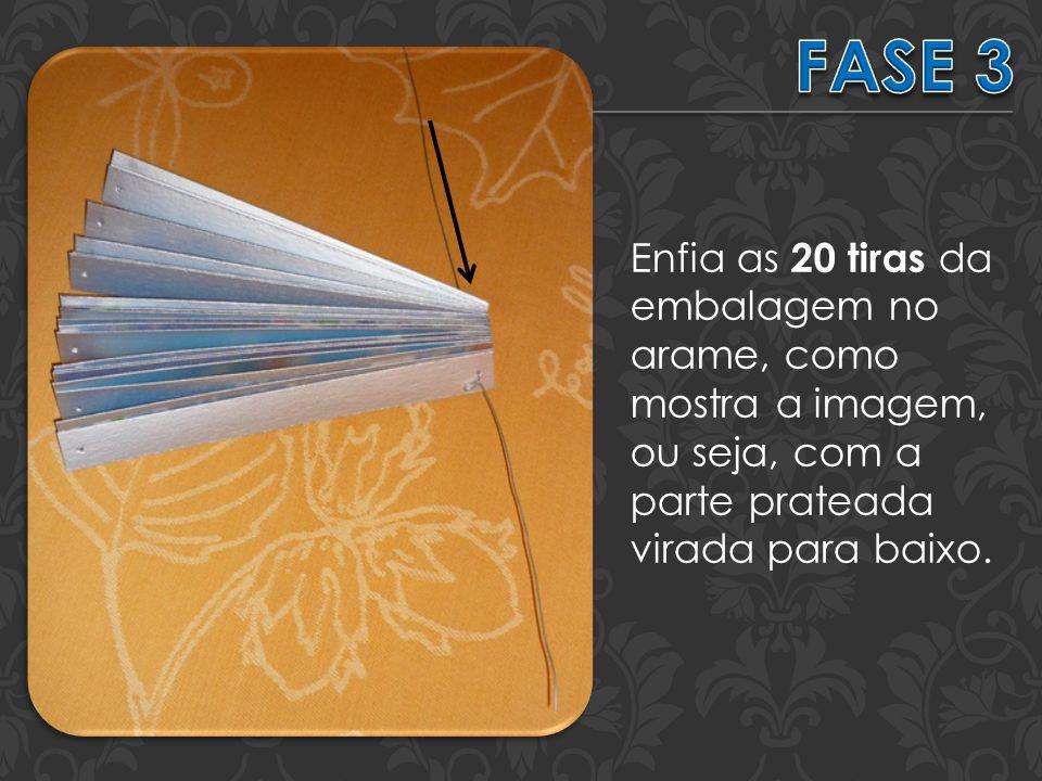 Enfia as 20 tiras da embalagem no arame, como mostra a imagem, ou seja, com a parte prateada virada para baixo.