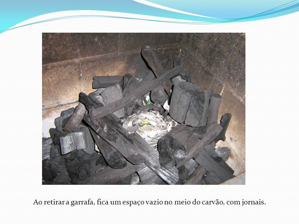 Ao retirar a garrafa, fica um espaço vazio no meio do carvão, com jornais.