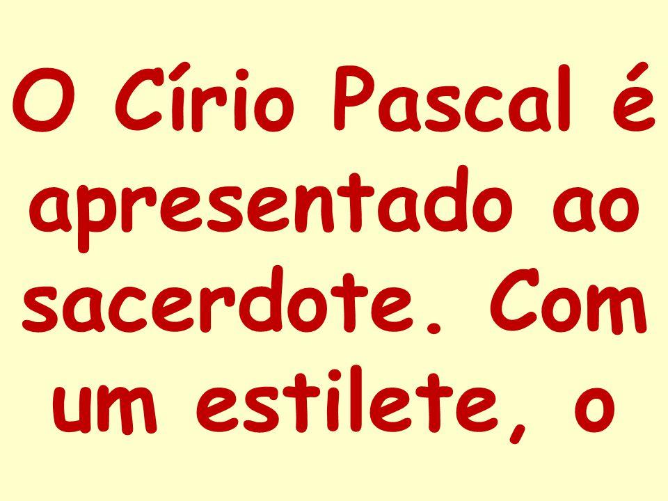 O Círio Pascal é apresentado ao sacerdote. Com um estilete, o