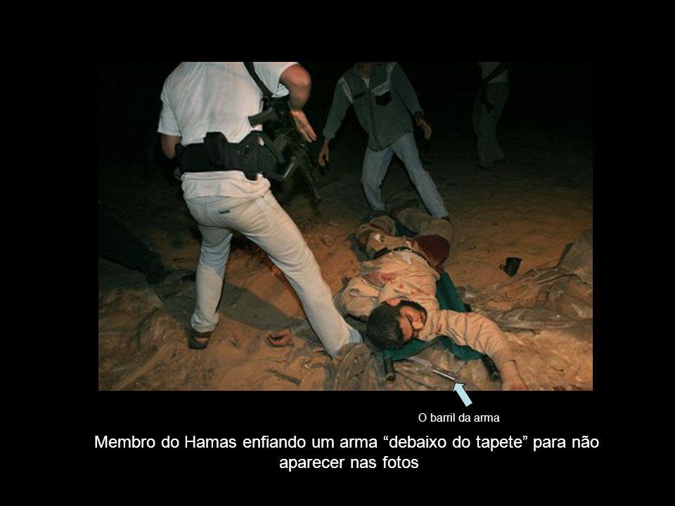 """Membro do Hamas enfiando um arma """"debaixo do tapete"""" para não aparecer nas fotos O barril da arma"""