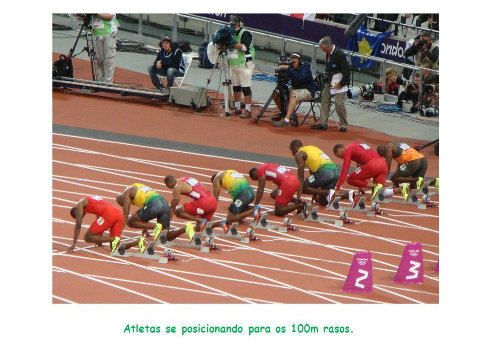 Atletas se posicionando para os 100m rasos.
