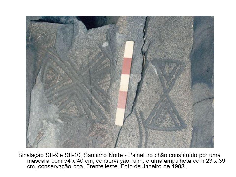 Sinalação SII-9 e SII-10, Santinho Norte - Painel no chão constituído por uma máscara com 54 x 40 cm, conservação ruim, e uma ampulheta com 23 x 39 cm